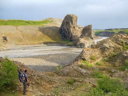 A father carrying his son in a kid carrier hike along the river in Vesturdalur Iceland