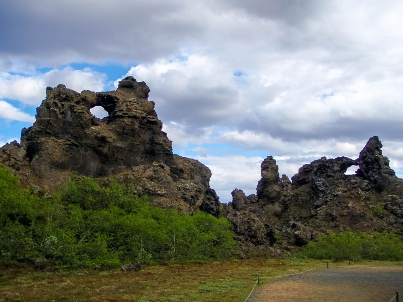 The mysterious arched lava rocks stand out from the green bushes in Dimmuborgir near Lake Myvatn Iceland