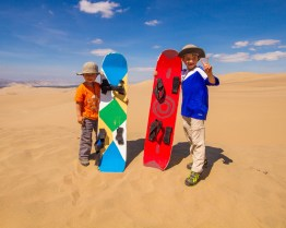 Two happy kids hold their sandboards in the desert of Huacachina, Peru