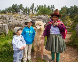 A Peruvian woman introduces two boys to her llama in Sacsayhuaman as they head to the ChocoMuseo in Cusco Peru