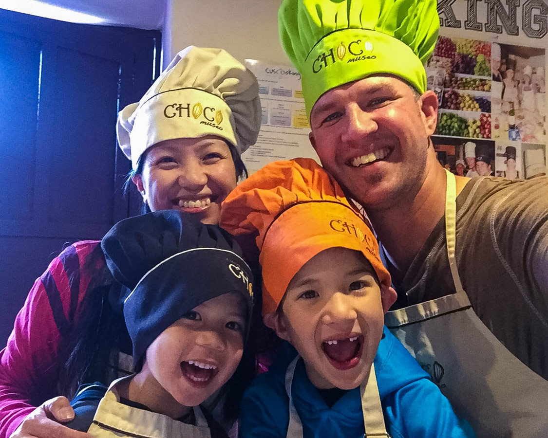 A young interracial family wearing colorful chef hats smiles during the ChocoMuseo in Cusco Peru