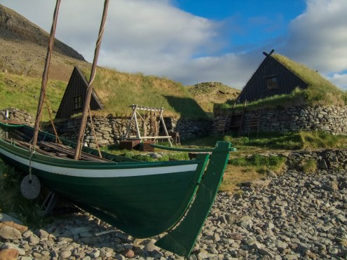 A wooden fishing boat sits in front of grass covered fishing huts on the coast of Iceland's westfjords