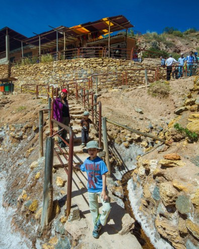 Family walking down the stairs towards the salt pans of Maras Peru