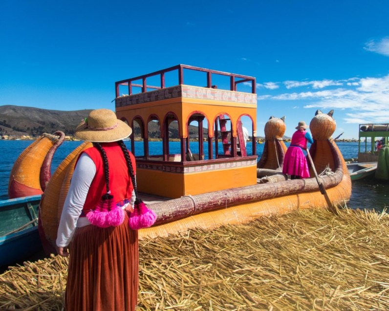 An Uros woman prepares to board a balsa reed boat on Lake Titicaca Peru. They can use these boats to transport families visiting Lake Titicaca with kids