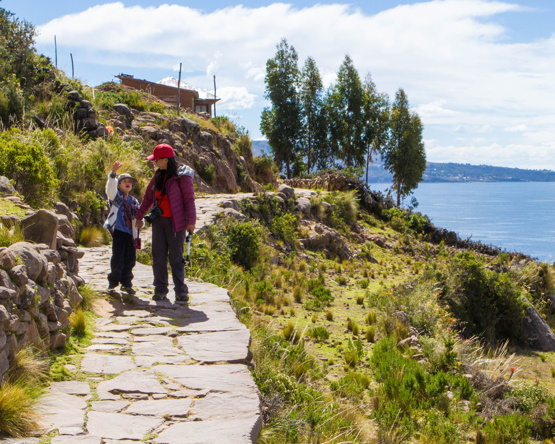 While visiting Lake Titicaca with Kids, a woman climbs up the steep walkways of Isla Taquile to visit the local people with her young son