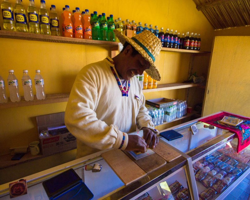 A Uru elder stamps a passport at the store on Isla de los Uros on Lake Titicaca