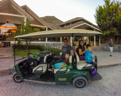 A family smiles while riding a golf cart along the paths of the Casa Andina Private Collection Sacred Valley Peru