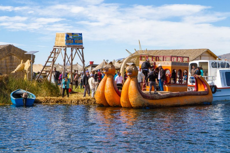 A floating reed island in Lake Titicaca with a reed lookout tower and a colorful balsa boat