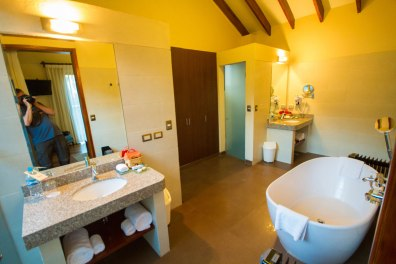 A stone sink and a deep soaker tub along with seperate shower and toilet rooms are featured in the ensuite washrooms of Casa Andina Private Collection Sacred Valley Peru