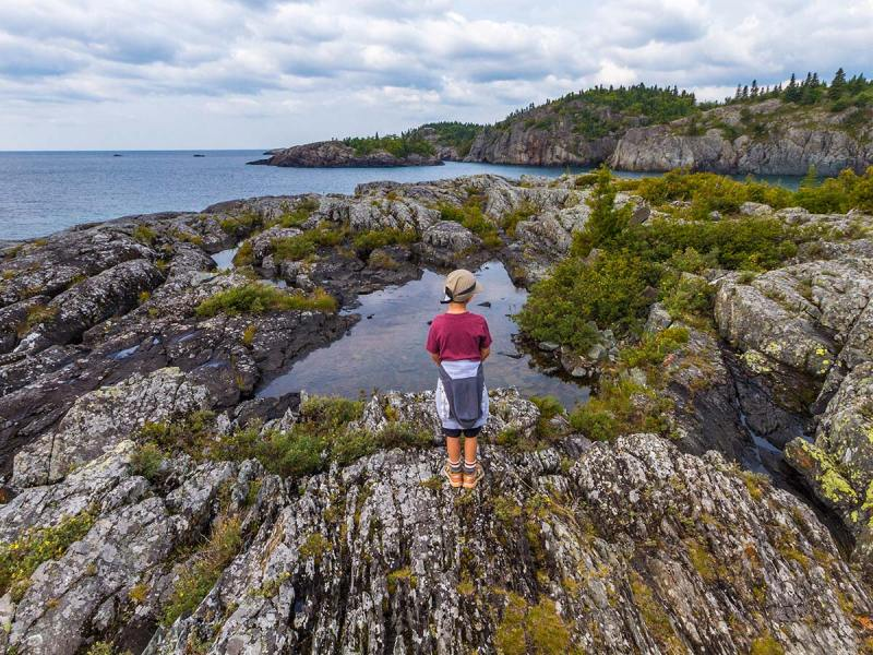 A young boy on a hike stands next to a pool of water at Lake Superior National Park in Ontario