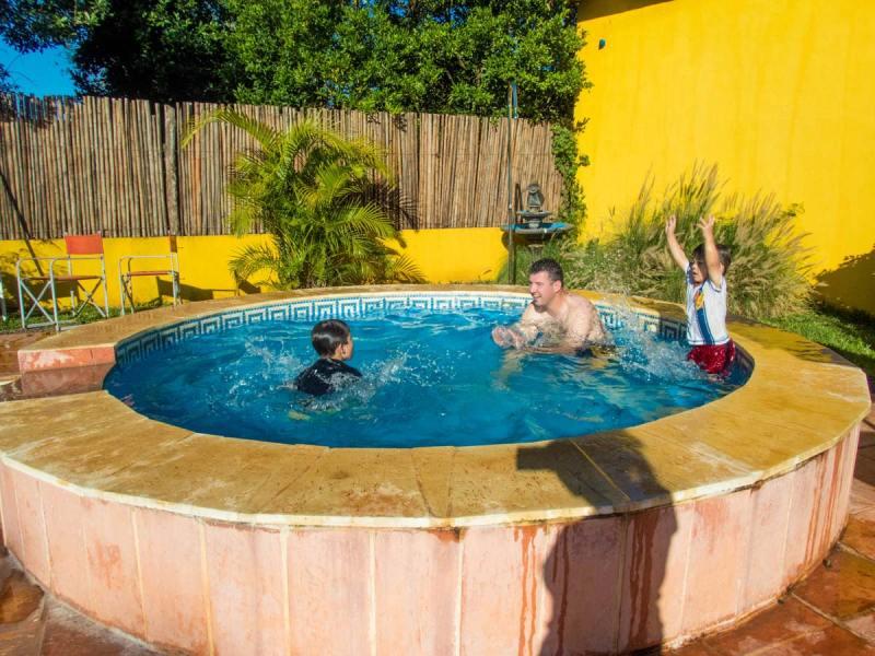 Man with 2 boys in a small circular pool in Brizas del Norte hotel in San Ignacio Argentina