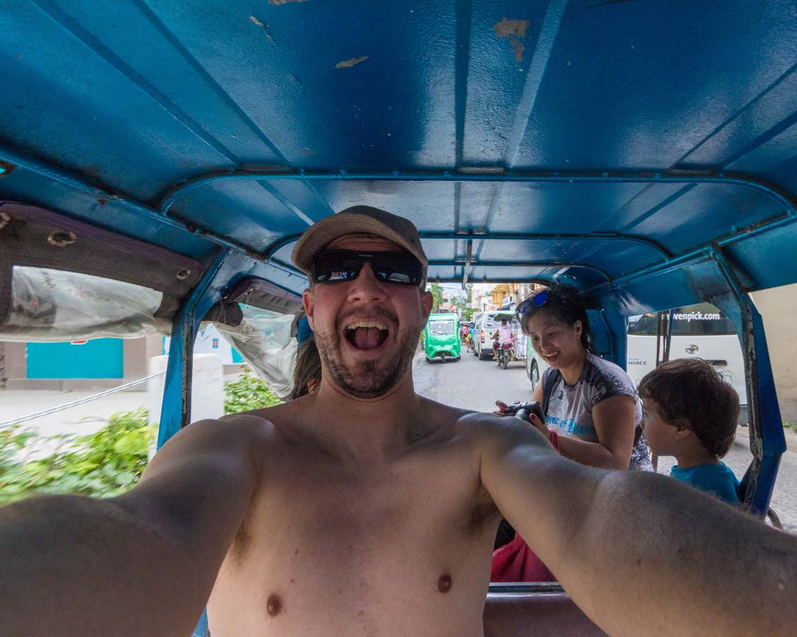 A man and his family ride a tuk tuk tricycle in Boracay Philippines