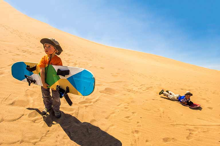 Children sandboarding in Huacachina Peru