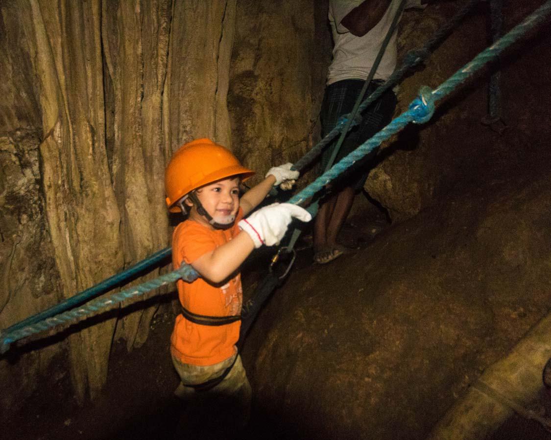 Boy climbing a rope ladder at Ugong Rock Caves in Palawan