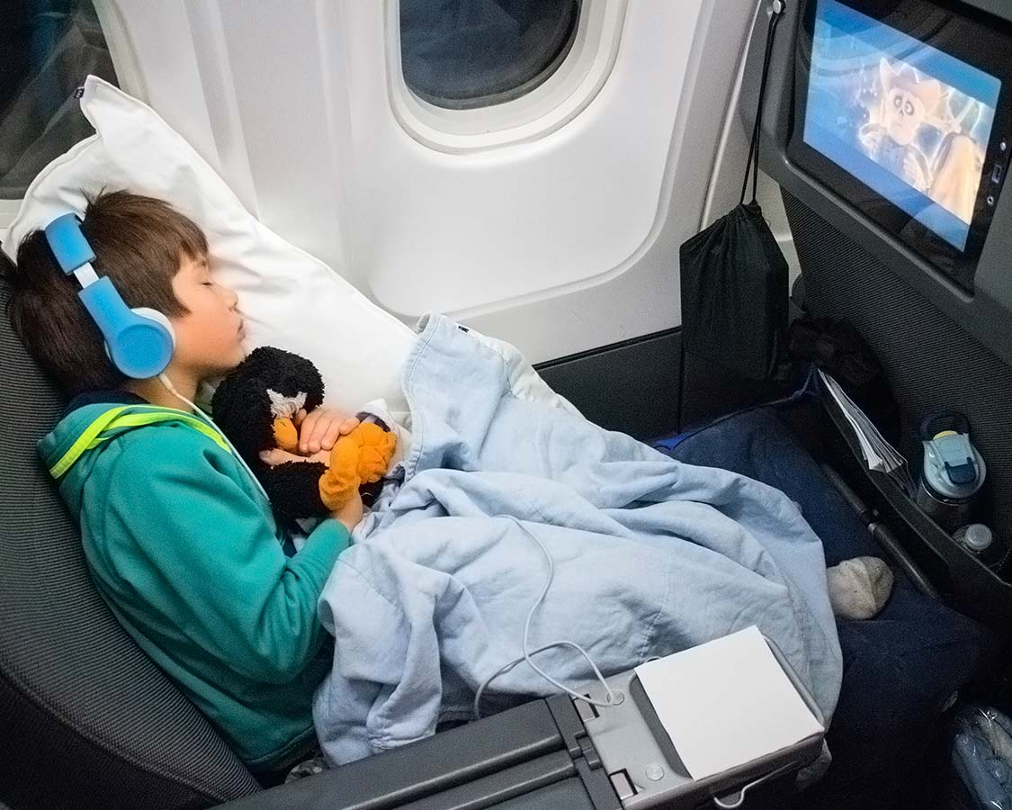 child sleeping on a plane using an inflatable footrest for plane