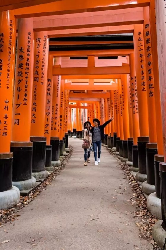 A young Japanese couple taking a selfie with the vermilion gates of Fushimi Inari shrine in Kyoto.