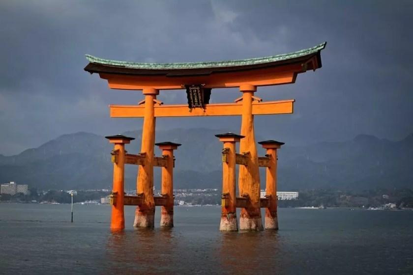 View of floating torii gate of Itskukushima shrine against a dark sky.