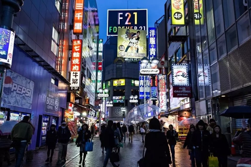 View of a street with noen lights in Tokyo's Shibuya district.