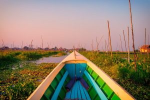 Colourful boat on Inle Lake in Burma in Maynamar with a pink sunrise