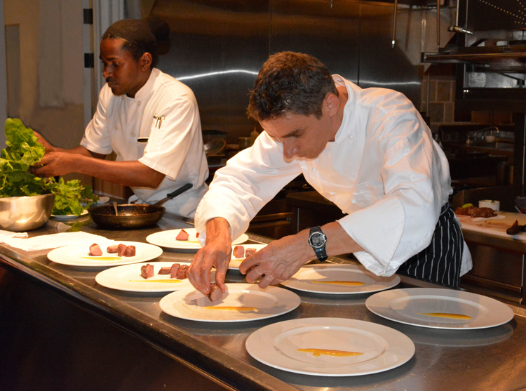 An image of Executive Chef Christophe Letard plating food at Belle Mont Farm