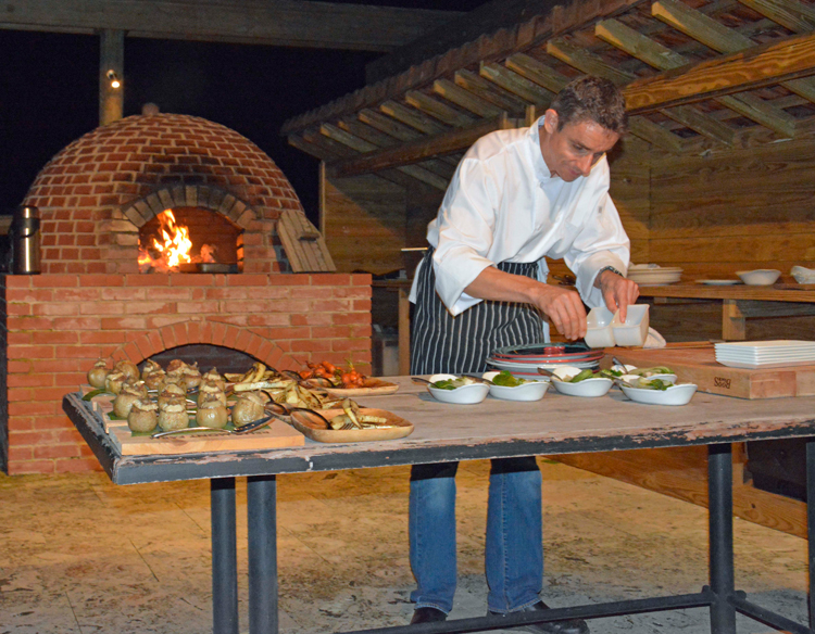 An image of Executive Chef Christophe Letard preparing dinner under the stars in the gardens at Belle Mont Farm