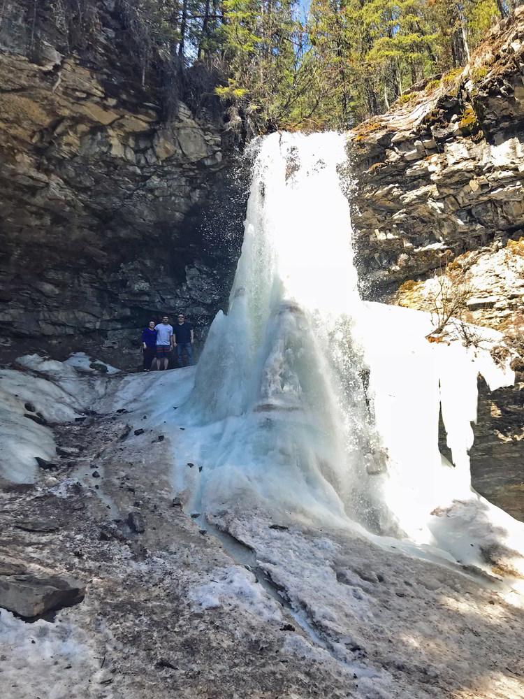 An image of three people standing behind the frozen Troll Falls in Kananaskis, Alberta