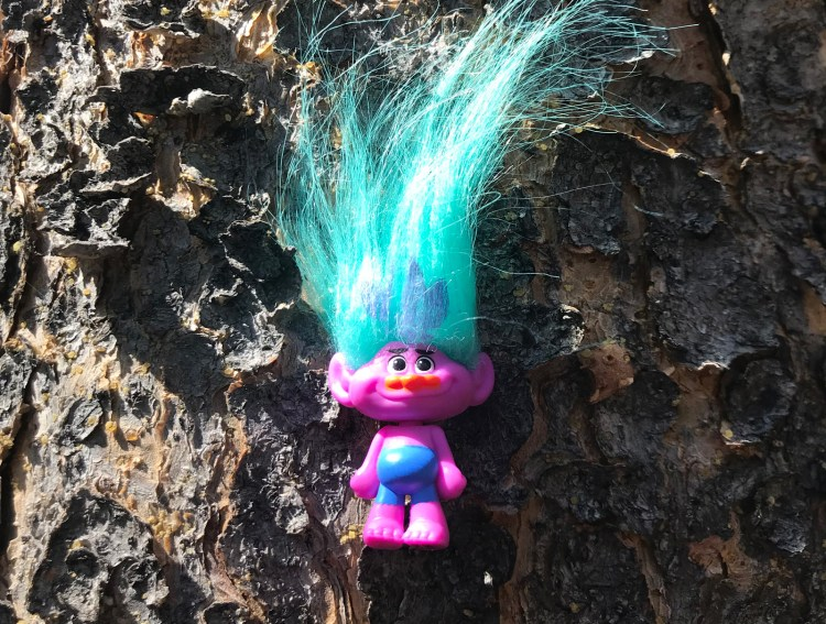 An image of a troll doll on a tree