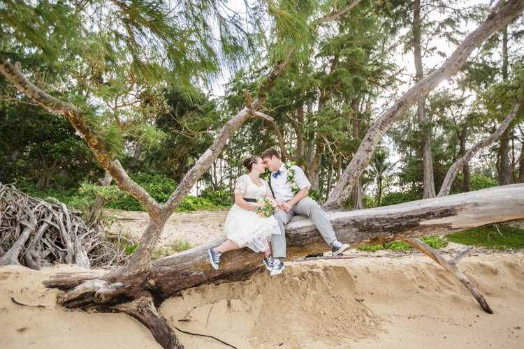 An image of a bride and groom sitting on a log on a beach in Hawaii