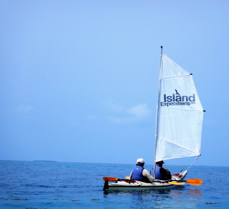 Image of a two paddlers in a double kayak with a sail in Belize