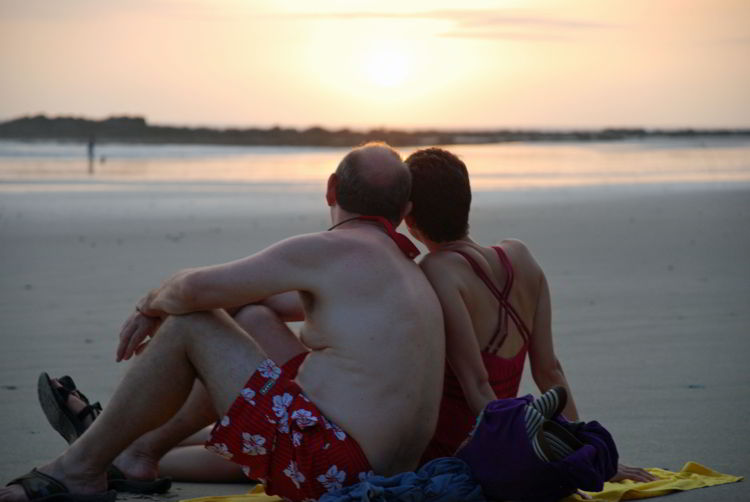 An image of a couple sitting on a beach in Costa Rica - Yoga Retreat Costa Rica