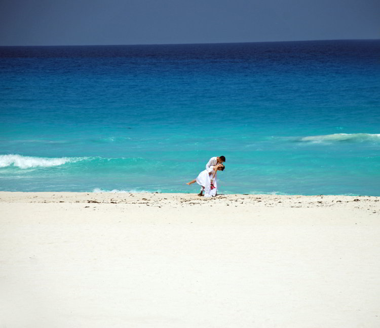 An image of a bride and groom kissing on a beach in Cancun, Mexico
