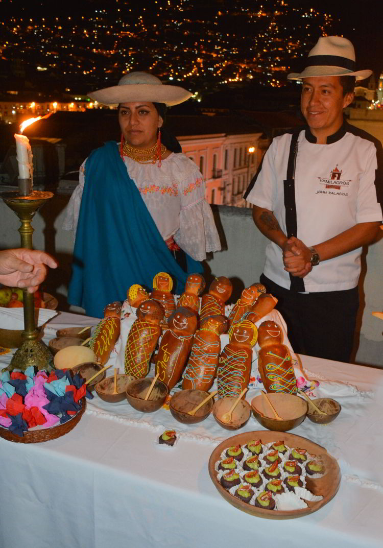 An image of two people standing behind a table filled with bread babies in Quito, Ecuador - Day of the Dead Festival -Dia de los Muertos