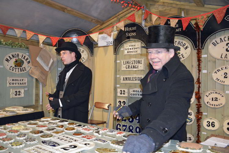 An image of two craft vendors in historic costume at the Lincoln Christmas Market in Lincolnshire, England