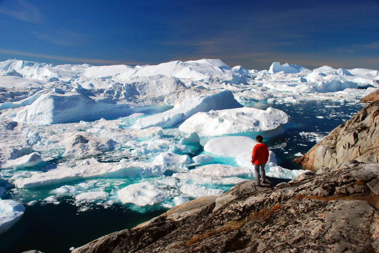 An image of a woman standing on a rock overlooking the Ilulissat Icefjord in Ilulissat Greenland