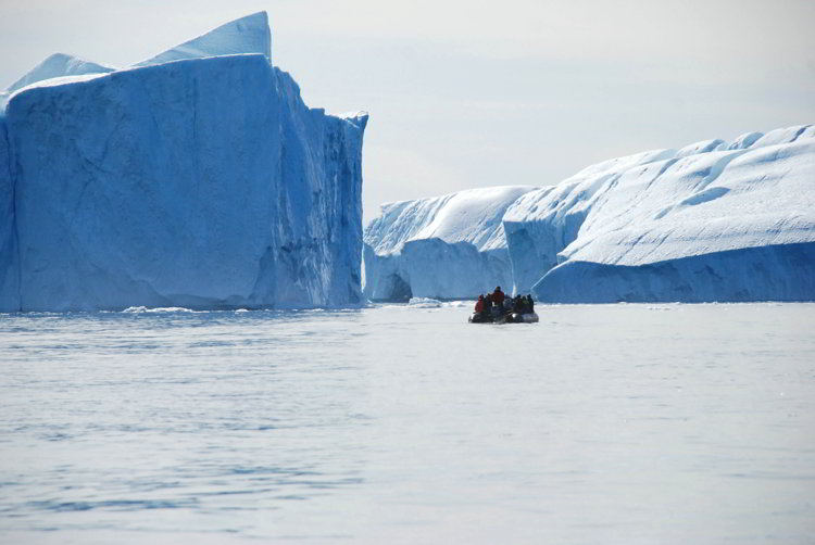 An image of a zodiac boat near large icebergs outside Ilulissat Greenland