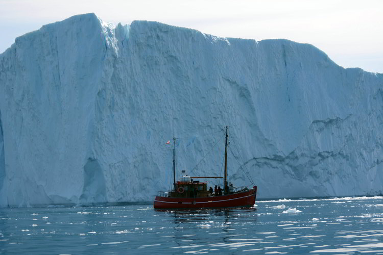 An image of a wooden boat in front of a large iceberg near Ilulissat Greenland