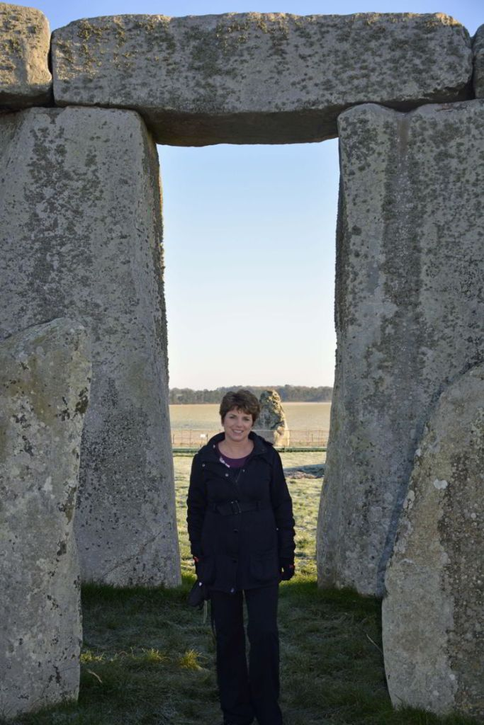 An image of a woman standing near the stones of the inner circle at Stonehenge near Salisbury, UK - Stonehenge inner circle tours