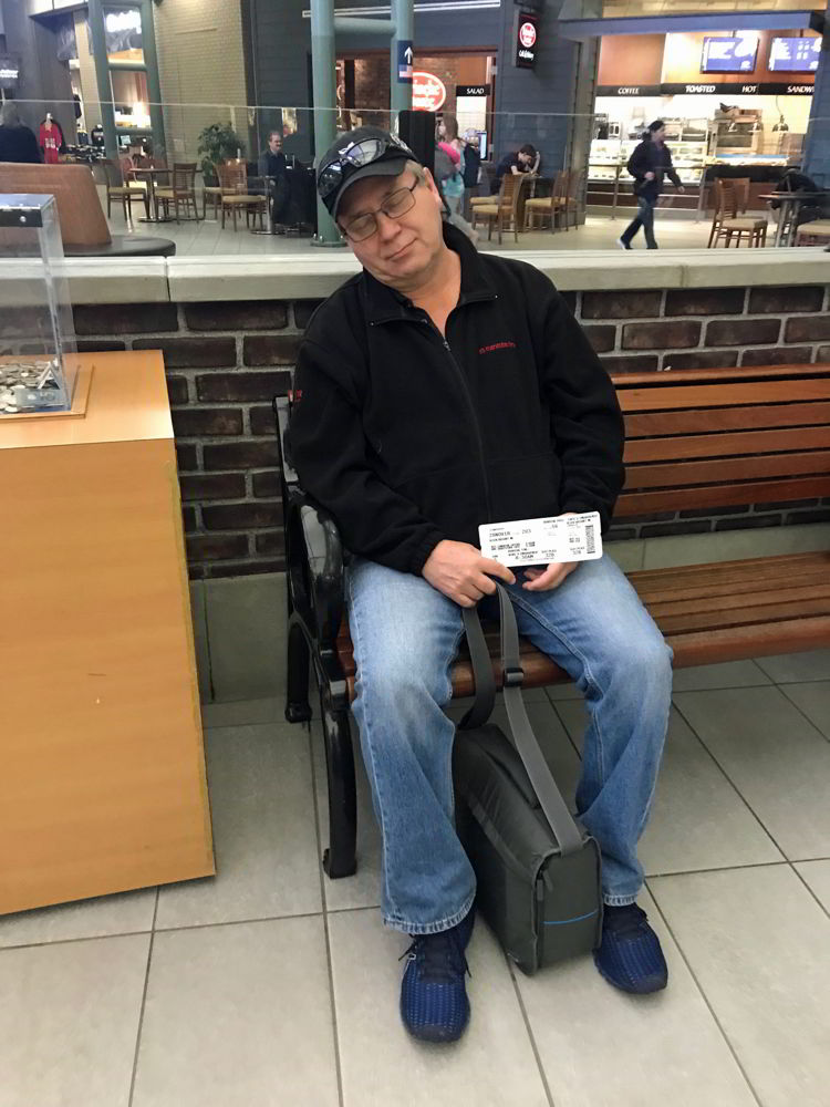 An image of a man sleeping at the airport - Swoop Airlines review