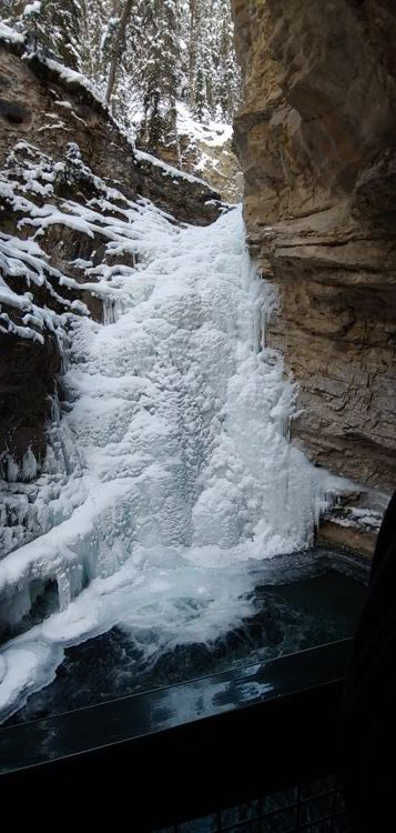 An image of the frozen lower falls in Johnston Canyon in  Banff National Park, Alberta - Johnston Canyon Winter Hike and ink pots hike