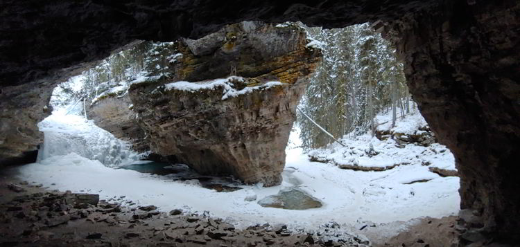 An image of a a frozen creek and waterfall in Johnston Canyon in Banff National Park, Alberta - Johnston Canyon Winter Hike and ink pots hike