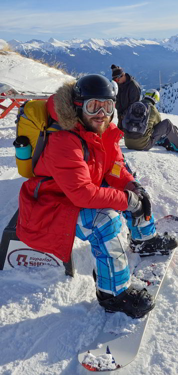 An image of a snow boarder sitting on a bench at Marmot Basin in  Jasper Alberta - Jasper Skiing