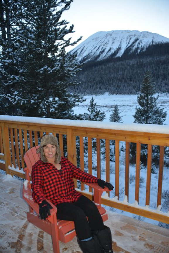 Image of a women sitting in a chair on a deck in the mountains - Avoid the Winter Blues.