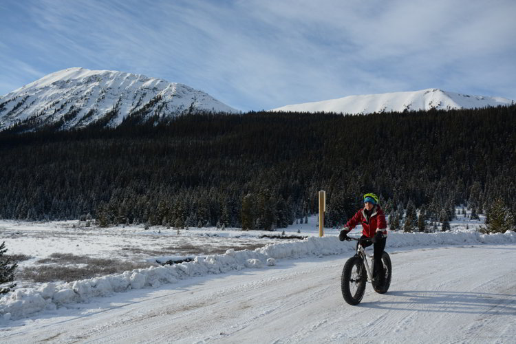 Image of a person riding a bike with large wheels in  the winter in Kananaskis Country - Avoid the Winter Blues