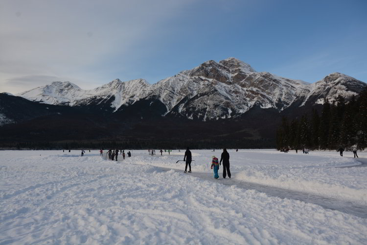 Image of people skating on Pyramid Lake in Jasper National Park - Avoid the Winter Blues.