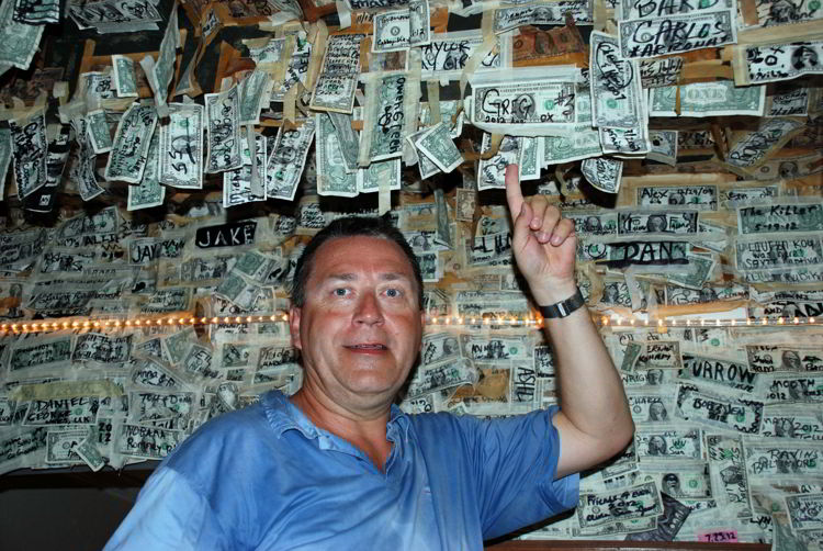 An image of a man pointing at a $1 bill he attached to the ceiling of the restaurant at Cabbage Key Inn and Restaurant - Cabbage Key Cheeseburger in Paradise
