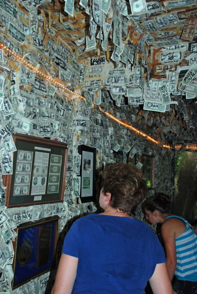 An image of a woman walking by the pictures of famous people putting $1 bills on the wall at Cabbage Key Inn and Restaurant - Cabbage Key cheeseburger in paradise