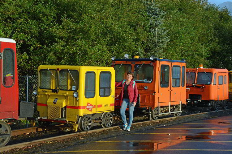 An image of a woman standing in front of some colorful rail motor cars in Seward, Alaska USA