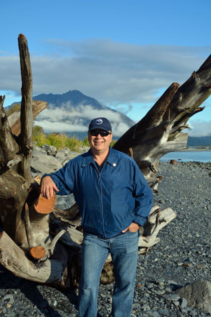 An image of a man standing in front of a large piece of driftwood on the shore of Resurrection Bay in Seward, Alaska USA