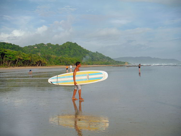 An image of a surfer carrying his board to the beach in Costa Rica.