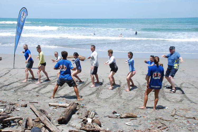 An image of a group of people practicing their surf stance at surf school in Costa Rica.